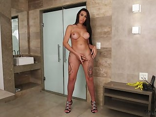 Slutty tanned tranny Gabrielly Soares is playing with fake boobs and hard cock